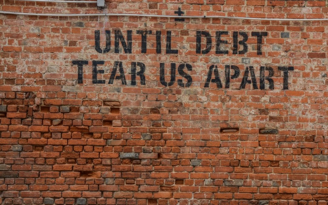 Brick wall with text until debt tear us apart about money and marriage